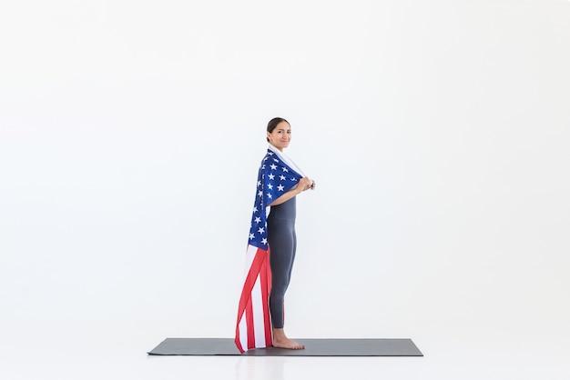 미국 국기를 가진 미국 여성이 매트 위에 서서 흰색 장면의 정면을 봅니다. 7 월 독립 기념일 개념의 4