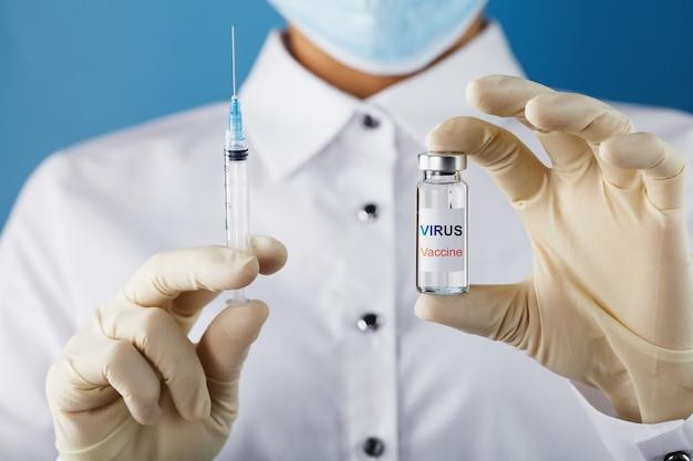 Ампула с надписью virus vaccine и шприц в руках ученого-врача