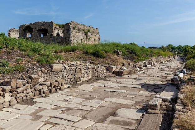 サイドの青い空を背景にしたレンガの小道の近くにある古代の廃墟となった建物。
