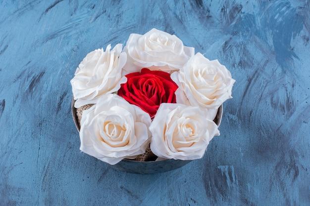흰색과 빨간색의 아름다운 신선한 장미가 있는 고대 그릇.