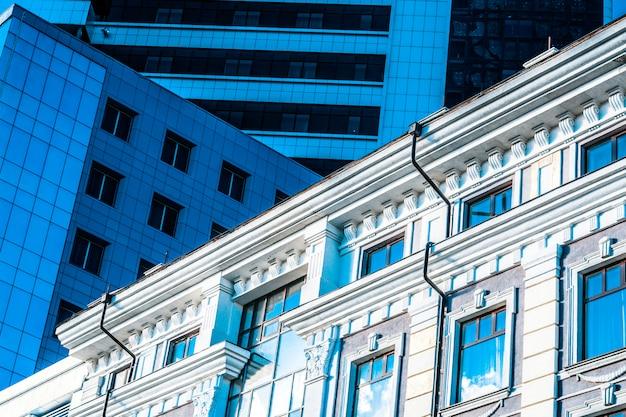 현대 오피스 빌딩 옆에있는 고대 건물. 건물의 현대적이고 역사적인 형태의 추상적 인 이미지