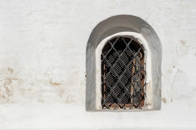 우크라이나 키예프 거리의 흰 벽에 있는 고대 창문. 오래 된 스타일의 창에 격자입니다. 구식 건축 개념입니다. 복사 공간