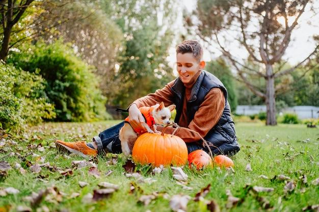 Девушка-андрогинная с короткой стрижкой держит собаку чихуахуа в оранжевом жилете. фото высокого качества