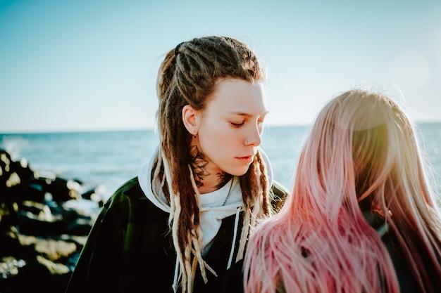 Андрогинная девушка с дредами и татуировкой на шее смотрит на девушку с розовыми волосами, стоящую позади нее на берегу моря.