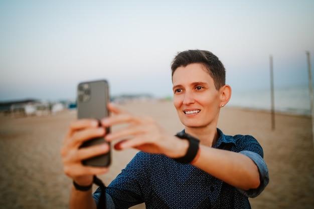 短い髪の両性具有の女性が微笑んで、ビーチで彼女の携帯電話を見る