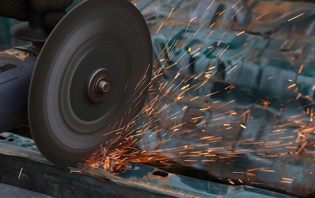 강철용 커팅 디스크가 있는 앵글 그라인더는 트림 블레이드로 차체를 절단하는 데 사용됩니다.