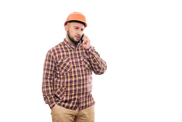 オレンジ色のヘルメットをかぶった怒って神経質な労働者が電話で大声で話し、電話に向かって叫んでいます。孤立した白い背景