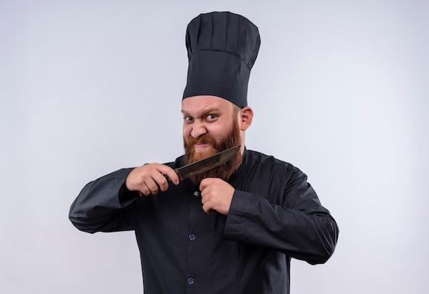 ナイフを持って白い壁のカメラを見ながら彼のひげをカットしようとしている黒い制服を着た怒っているひげを生やしたシェフの男