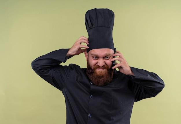緑の壁に頭を抱えて携帯電話で話している黒い制服を着た怒っているひげを生やしたシェフの男