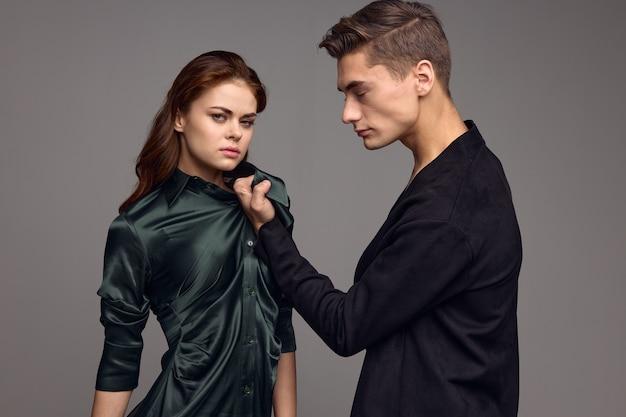 화난 남자는 회색 가정 폭력에 드레스 칼라로 여자를 안고 있습니다.