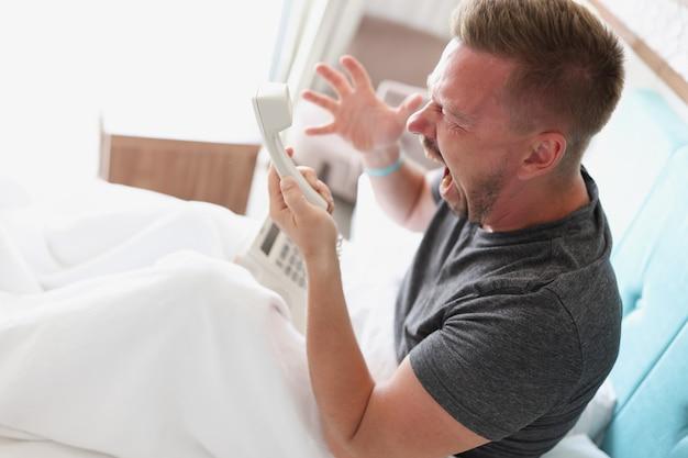 Злой мужчина сидит на кровати и кричит в телефон, крупный план. недовольство гостиничным сервисом