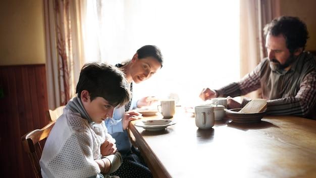Сердитая маленькая девочка с родителями дуется в помещении за столом у себя дома, концепция бедности.