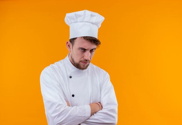 オレンジ色の壁を見ながら手を組んで白い制服を着た怒っている若いひげを生やしたシェフの男