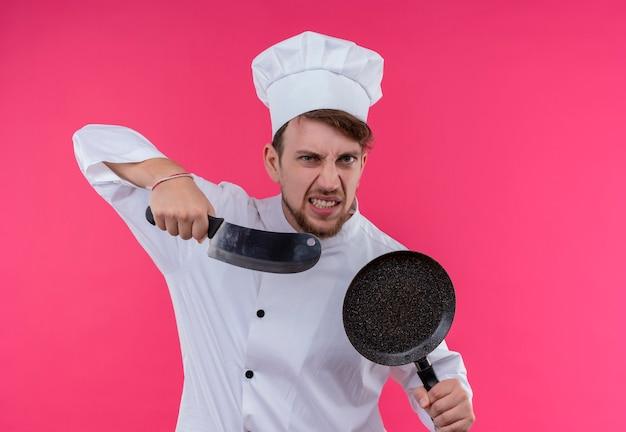 ピンクの壁を見ながらフライパンで肉切り包丁を保持している白い制服を着た怒っている若いひげを生やしたシェフの男