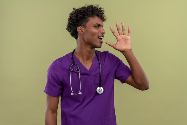 Сердитый молодой красивый темнокожий доктор с вьющимися волосами в фиолетовой форме со стетоскопом зовет кого-то, глядя в сторону на зеленом пространстве