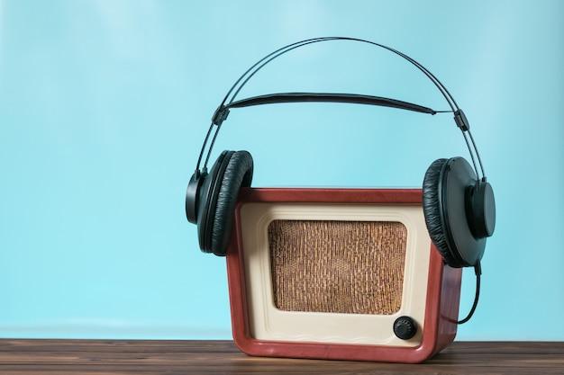 파란색 배경에 나무 테이블에 검은 헤드폰을 입은 골동품 라디오 수신기. 사운드 및 비디오 재생 기술.
