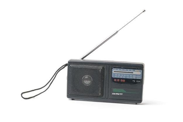 白い背景で隔離された拡張アンテナを備えたアンティークのラジオ受信機。ヴィンテージラジオ機器。