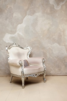 壁にアンティークの白い椅子。アンティークの革張りの椅子。椅子に縞模様の枕があります