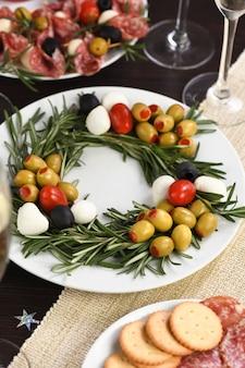 オリーブとベビーモッツァレラチーズとチェリートマトを詰めたローズマリーの前菜。クリスマスリースの形で作られました。