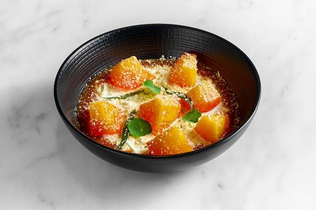 식욕을 돋우는 특이한 이탈리아 디저트-감과 잼을 곁들인 stracciatella di bufala, 대리석 표면에 검은 색 접시에 담아 제공