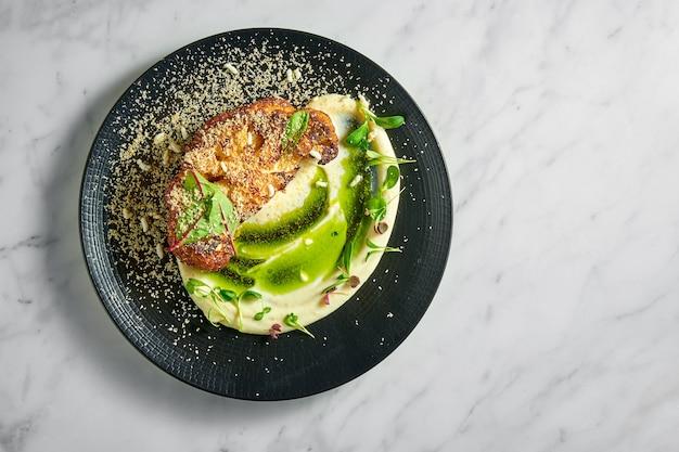 Аппетитное диетическое блюдо - стейк из цветной капусты с картофельным пюре и зеленым маслом, подается в черной тарелке на мраморной поверхности.