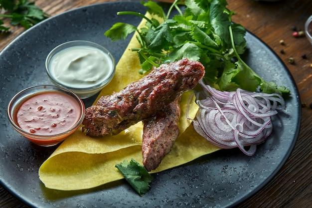 Аппетитное блюдо турецкой кухни - куриный шашлык из фарша с лавашем, кинзой, луком и соусами, который подается в синей тарелке на деревянном столе. ресторанная еда. крупным планом вид