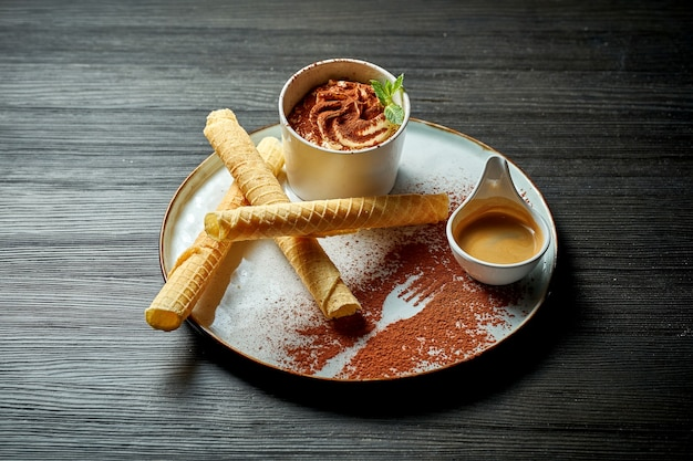 Аппетитный итальянский десерт - тирамису с порцией эспрессо. деревянный фон