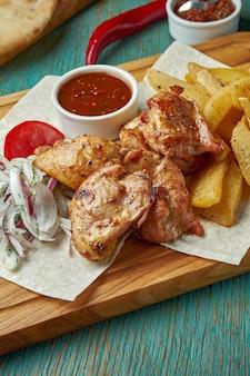 식욕을 돋우는 동양 요리-구운 닭고기 또는 쇠고기 케밥과 감자 반찬과 녹색 테이블에 붉은 양파를 곁들인 양파. 그루지야 요리. 시시 케밥