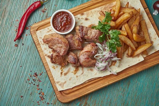 식욕을 돋우는 동양 요리-구운 돼지 고기 케밥과 감자 반찬, 양파와 녹색 테이블에 양파. 그루지야 요리. 시시 케밥
