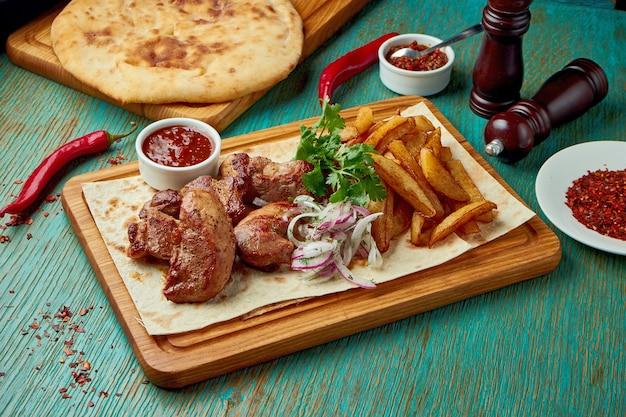 Аппетитное восточное блюдо - шашлык из свинины на гриле с гарниром из картофеля и лука с красным луком на зеленом столе. грузинская кухня. шашлык