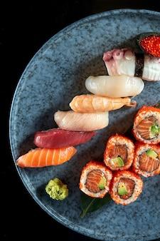 鮭、アボカド、とびこキャビアを添えた、さまざまなにぎりと裏巻きで構成された食欲をそそる寿司セット。日本の伝統料理。食品デリバリー。黒で隔離