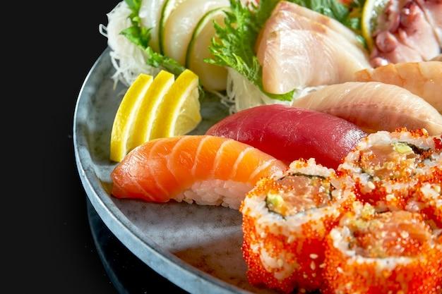 Аппетитный суши-сет, состоящий из разнообразных нигири. сашими и урамаки с лососем, авокадо и икрой тобико. японская традиционная кухня. доставка еды. изолированные на черном Premium Фотографии