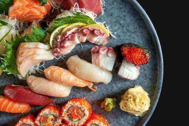 Аппетитный суши-сет, состоящий из разнообразных нигири. сашими и урамаки с лососем, авокадо и икрой тобико. японская традиционная кухня. доставка еды. изолированные на черном