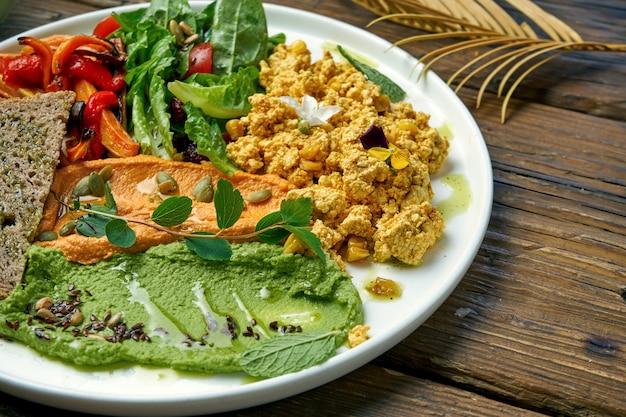 食欲をそそるベジタリアン料理は、豆腐チーズ、焼きピーマンとルッコラのサラダ、2種類のフムスのスクランブルです。木材