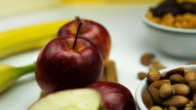 Яблоко, орехи и бананы на белом.