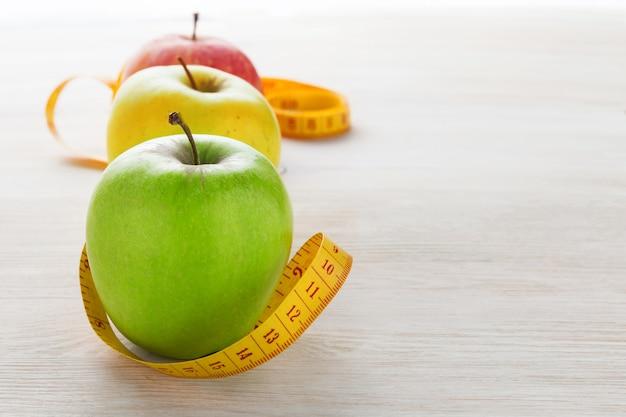 Яблоко на деревянном фоне и измерительная лента. концепция здорового образа жизни. копировать пространство