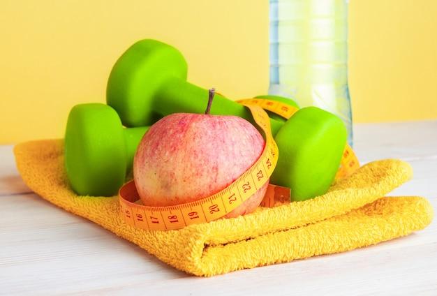 ダンベルと巻尺のある木製の背景にリンゴ