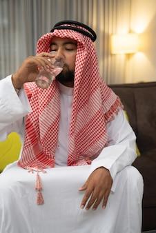 彼の断食を壊すときガラスとターバン飲料水でアラブ人