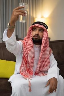 ターバンに乗ったアラブ人が水で満たされたグラスを持ち上げ、それを持ち上げて見られるようにします