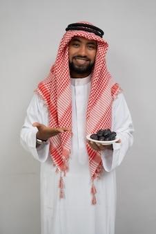 ターバンを着たアラブ人は、ナツメヤシのプレートを持って微笑んで、もう一方の手でそれを提供します