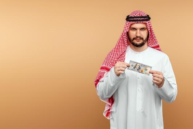 Араб в национальном костюме держит в руках доллары.