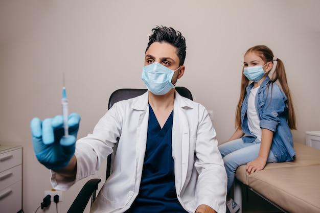 Арабский или турецкий врач готовится сделать прививку от коронавируса. маленькая девочка на заднем плане. фото высокого качества