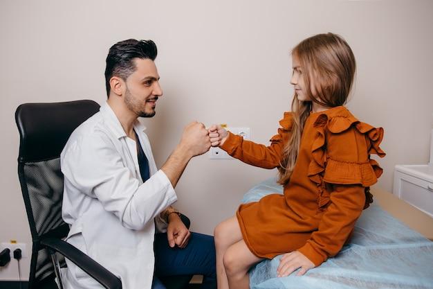 Арабский или турецкий педиатр обменивается рукопожатием с маленькой девочкой перед обследованием. фото высокого качества