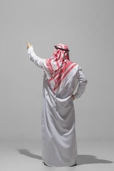 灰色のスタジオで隔離の後ろ姿をポーズするアラブ人