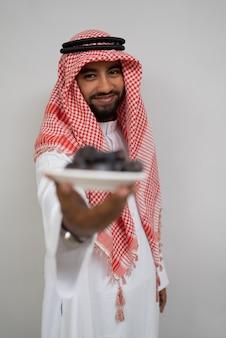 ターバンを着たアラビア人が、カメラにナツメヤシのプレートを運び、提供している間、微笑みます