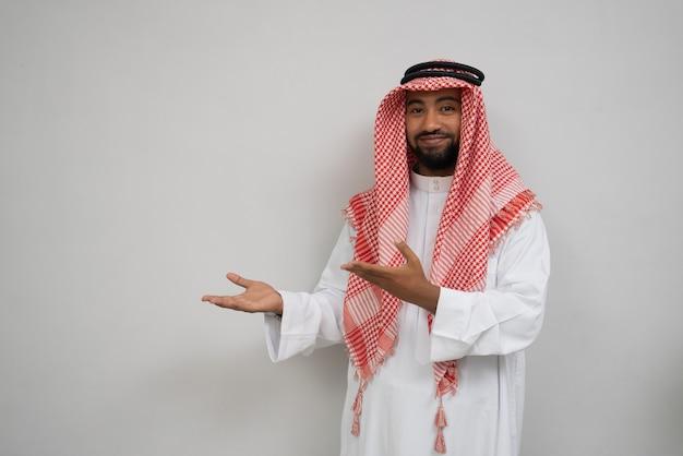 Арабский молодой человек в тюрбане улыбается, стоя, глядя в камеру, жестом руки пр ...
