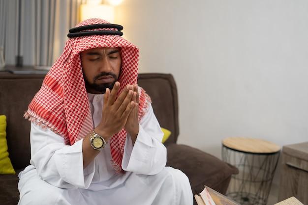 Арабский молодой человек молится с поднятыми руками