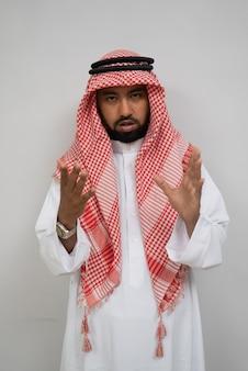 Арабский молодой человек, стоящий и смотрящий в камеру с жестами рук во время разговора