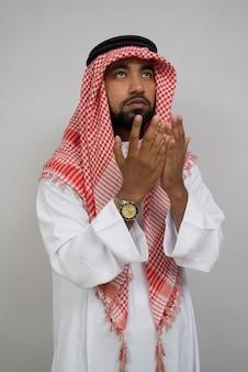 Арабский мусульманский тюрбан молится с поднятыми вверх обеими руками