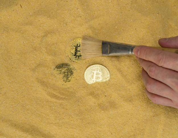 ブラシを持った考古学者が金色の砂のビットコインコインをクリアしますマイニング暗号通貨